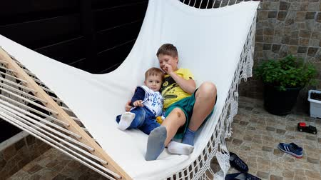 dojem : 4k video of happy smiling toddler boy lying and playing with elder boy in hammock at house backyard Dostupné videozáznamy