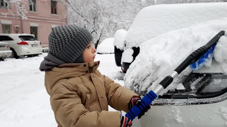 vassoura : 4k video of toddler boy cleaning car from snow with brush Child helping cleaning vehicle in morning after blizzard Vídeos