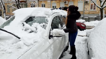 klíring : 4k video of beautiful smiling young woman cleaning her car from snow with telescopic brush