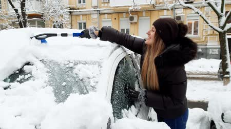 telescopic : 4k footage of beautiful smiling young woman removing snow from her automobile with brush. Driver cleaning car after snowstorm.