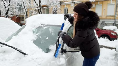 telescopic : 4k footage of smiling young woman cleaning her car from snow before riding to work Stock Footage