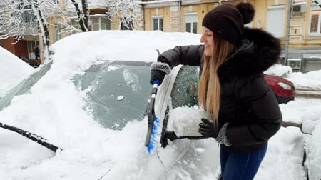 Łopata : 4k video of beautiful smiling young woman removing snow from her car with brish on the parking lot
