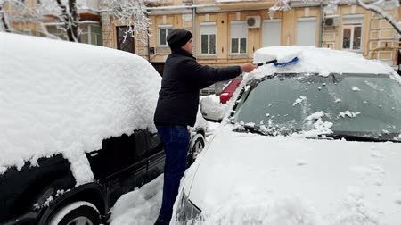 süpürge : 4k footage of young man removing snow from his car at morning before riding to work
