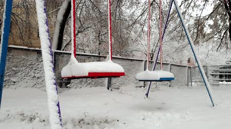 тишина : 4k footage of empty swings on playground covered in snow swaying by wind