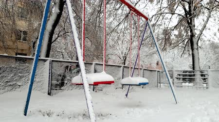 griezelig : 4k footage of swings on playground covered in snow after blizzard at winter. No kids are playing around