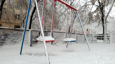 меланхолия : 4k footage of empty swings on playground covered in snow swaying by wind
