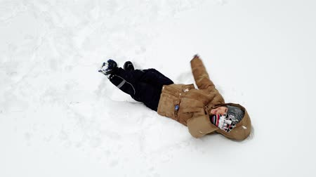snow caps : 4k video of cheerful todler boy lying on snow at park and laughing