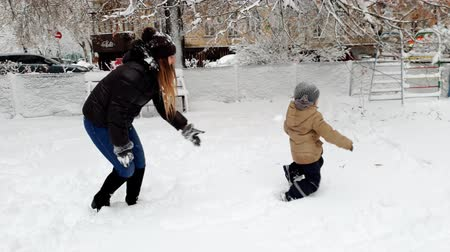 travessura : 4k video of young mother playing with her toddler son in winter park and throwing snowballs Vídeos