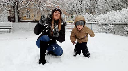 travessura : 4k video of laughing toddler boy playing with young mother on playgrund covered with snow. Family throwing snowballs