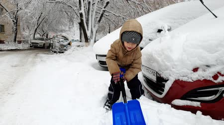 snow removal : 4k footage of happy smiling toddler boy digging snowdrifts on car parking with big snow shovel