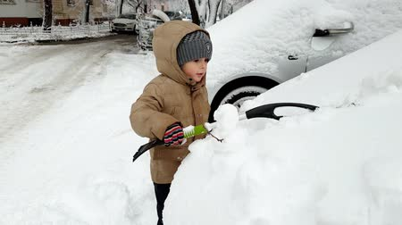 сугроб : 4k video of 3 years old toddler boy helping cleaning car covered in snow after snowstorm