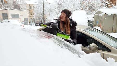 süpürge : 4k video of beautiful female driver cleaning her car from snow after blizzard at morning