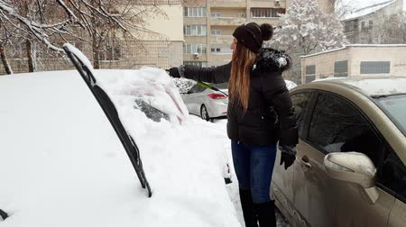 geada : 4k footage of smiling young woman cleaning her car from snow before riding to work Stock Footage