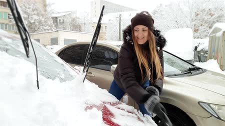 snow removal : 4k video of smiling female driver removing snow from her car at morning after snowstorm