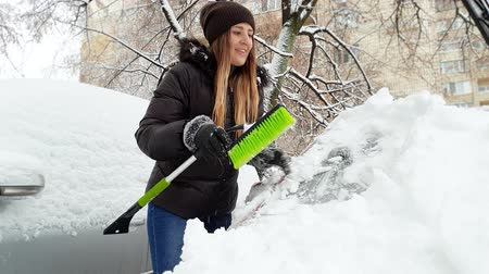 telescopic : 4k footage of young smiling woman cleaning telescopic brush from snow after removing snow from her car