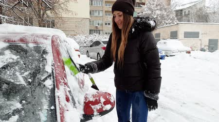 telescopic : 4k video of beautiful smiling young woman cleaning her car from snow with telescopic brush