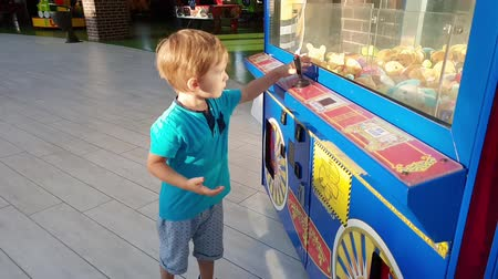 ticket machine : 4k video of little toddler boy playing with coin operated machine at amusement park. Child trying to win soft toy by picking it with claw