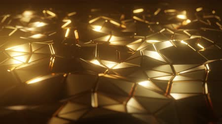 Abstract 3D visualization of a geometric low-poly golden surface. Computer animation loop. Modern background with polygonal gold shape. Loopable motion design 4k UHD Stock Footage