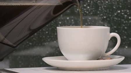 stabil : coffee pouring into a white cup with  rain windows as background Stock mozgókép