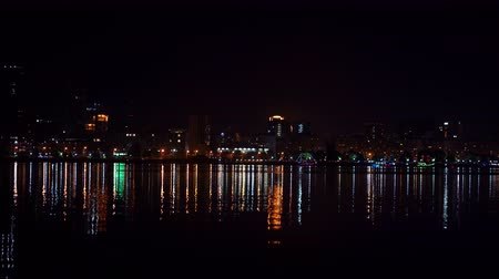 night cityscape with reflection in the water. Many colored lights and lamps.