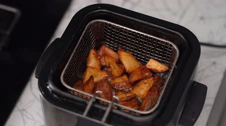 batatas fritas : lower the basket of potatoes into deep-frying boiling oil Stock Footage