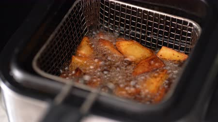 batatas fritas : basket of potatoes into deep-frying boiling oil Stock Footage