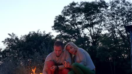 Young couple sitting neer bonfire in the forest. Romantic and happy couple relationships. Romance couple. Youth lifestyle, man and woman in love Stock Footage