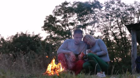 Young couple sitting neer bonfire in the forest. Romantic and happy couple relationships. Romance couple. Youth lifestyle, man and woman in love Filmati Stock