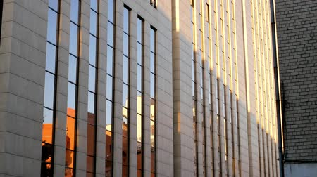 Beautiful tall concrete and glass building at sunset Stock Footage