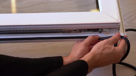 izolace : The professional master changes the rubber gaskets and seals on the pvc window. Preparing for winter, warming the house. Window repair. Window sealing