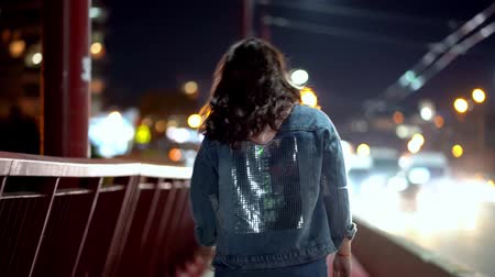 A young woman walks in the night city on the background of lights and the road
