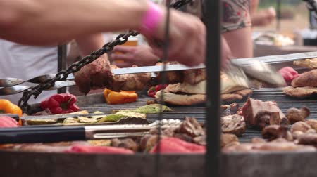 patlıcan : The cook turns the meat and mushrooms on the grill. Street food festival
