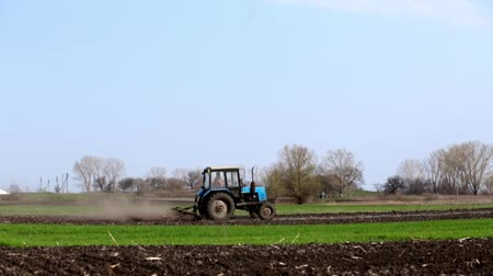 A tractor plows a field. Blow pulling a dust