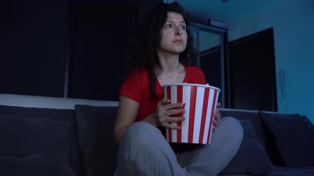 Girl in the evening on the couch watching a horror movie on TV. Eating popcorn from a bucket. Scared and hiding behind a bucket of popcorn