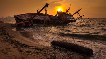 hajótest : wreck fishing boat near Pattaya beach at sunset time with plastic waste or garbage on sand and rock beach