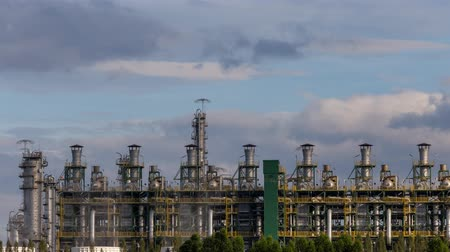 distillation : time lapse of petroleum and petrochemical plant for chemical product in industrial zone for business with moving of rainy cloud