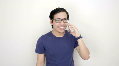 délkelet Ázsia : Happy Asian Man Wearing Glasses Calling With Smartphone On Studio White Background 4K Resolution Stock mozgókép