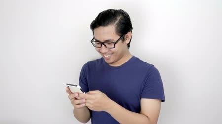délkelet Ázsia : Happy Asian Man Texting With Smartphone On Studio White Background 4K Resolution Stock mozgókép