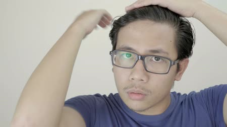 délkelet Ázsia : Young Asian Man Arranges His Hair Using Hand in front of Camera 4K Resolution