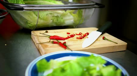 chili paprika : Sliced Chili Lettuce on Cutting Board with White Knife 60 fps Stock mozgókép