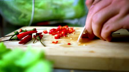 vágás : Man Cutting Chili Lettuce on Cutting Board with Ceramic White Knife - Close Up 60 fps Stock mozgókép