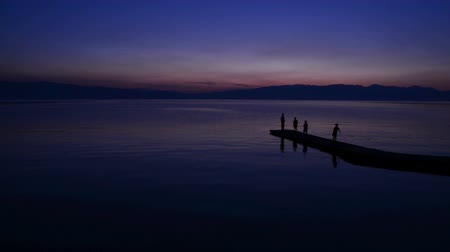 serene : People enjoy sunset at calm lake in Ohrid, Macedonia.