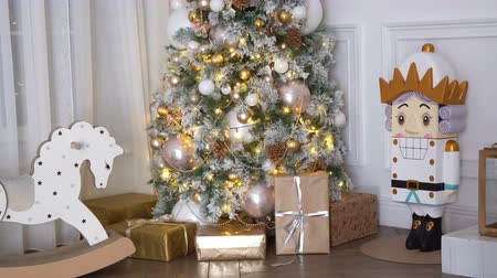 christmas ball gold : 4K footage of New Year tree decorated with present boxes and gifts, rocking horse and nutcracker