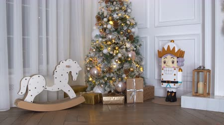golden ribbon : 4K footage of New Year tree decorated with present boxes and gifts, rocking horse and nutcracker