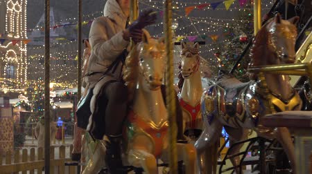 Moscow, Russia - January, 2018: Carousel with rocking horses on christmas market in Moscow, Russia