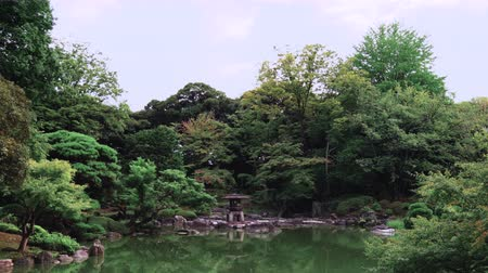kanto district : Pan video of Tokyo Metropolitan Park KyuFurukawas Japanese Gardens Yukimi stone lantern overlooking shinji pond in summer.