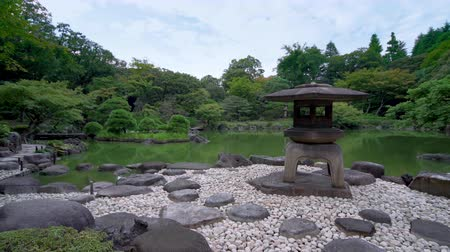 kanto : Pan video of Tokyo Metropolitan Park KyuFurukawas Japanese Gardens Yukimi stone lantern overlooking shinji pond in summer.