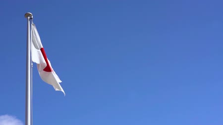 árbocszalag : Real-time video of the Japanese National Flag waving in the wind against a cloudless blue sky in Japan where Tokyo is the host city for the international sporting events in summer 2020.