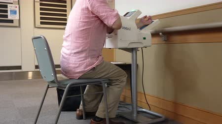 megelőzés : Tokyo, Japan - February 14 2020: Video of a man from behind sitting taking his blood pressure with a self service blood pressure monitor in Japan.