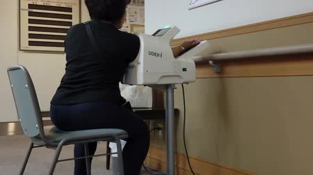 Tokyo, Japan - February 14 2020: Video of a woman from behind sitting taking his blood pressure with a self service blood pressure monitor in Japan.
